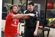 Professional trainer Trevor instructs an athlete on the proper use of kettle bells.